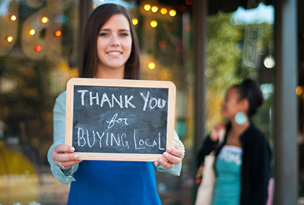 Thank you for buying local on a sign, held by a woman.