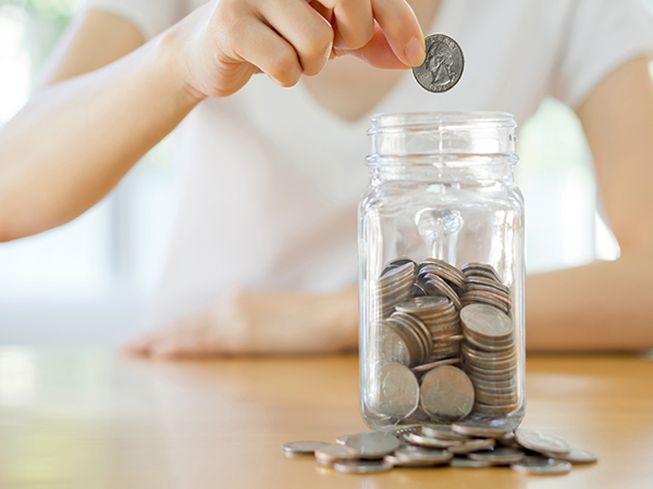 Person holding a quarter above a glass jar filled with coins. It appears the person will be placing the coin in the jar. They are indoors wearing casual attire.