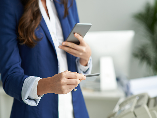 Women holding cell phone and credit card, who appears to be making a payment on her phone indoors. She is wearing professional attire and her face is outside the frame.